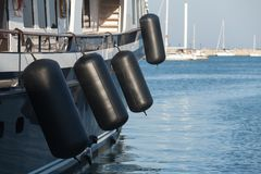 Black rubber inflatable ship fenders. Hanging above sailing yacht hull Royalty Free Stock Images