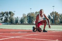 Black runner in position at start Stock Photography