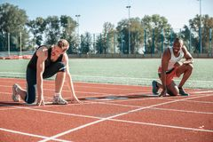 A black runner and a white man are having fun at the start royalty free stock photo