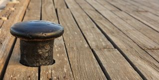 Black bollard mooring on wooden deck background. Closeup view with details, Copy space Stock Photography