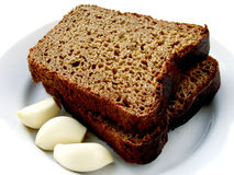 Black rye bread and garlic. Two slices of black rye bread and some cloves of garlic on white plate Stock Photography