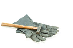 Black safety work glove and hammer Royalty Free Stock Photography