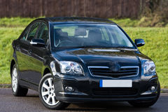 Black saloon Car. Against a grass background Royalty Free Stock Photo