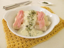 Black salsify roots with bechamel sauce and cooked ham. Black salsify roots with bechamel sauce, cooked ham and herbs stock images