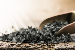 Black salt. Wooden scoop with black salt on table stock photography