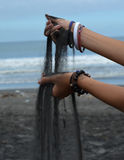 Black sand. Pouring from hands Stock Photo