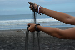Black sand. Pouring from hands Royalty Free Stock Photo