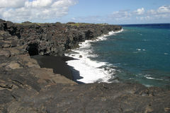 Black Sand Beach. A small cove on the Big Island of Hawaii reveals a black sand beach Stock Photos