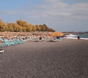 Black sand beach with chairs. And ocean waves in Greece Royalty Free Stock Image