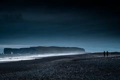 Black Sand Beach, Iceland dark night during sunrise with couple walking. Black Sand Beach Iceland during dark night sunrise with couple walking on the beach stock photo