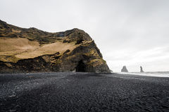 Black Sand Beach in Iceland with Ocean Water And Rock Lava Mountain. Royalty Free Stock Photo