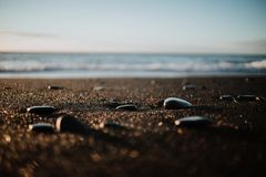 A black sand beach in Iceland. Some stones at a black sand beach in Iceland at sunset stock image