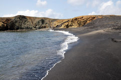 Black sand beach known as nesting ground for turtles. Waves roll in to a black sand beach found in Djeu, popular for being nesting ground for sea turtles royalty free stock photography