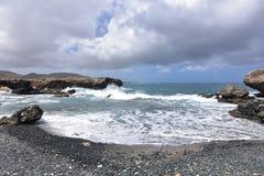 Black Sand Beach with Lava Rock on the Coast of Aruba Stock Image