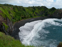 Black sand beach in Maui Hawaii. Black sand beach  with palm trees and lush green plants. Heavy surf. Maui Hawaii Stock Photo