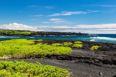 Black Sand beach on the Big Island of Hawaii; black volcanic rock and vegetation in foreground, blue ocean and waves in background royalty free stock photo