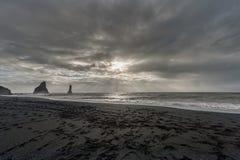 Black Sand Beach Reynisfjara in Iceland. Rocks in Water. Ocean Waves. Sunlight. Royalty Free Stock Image
