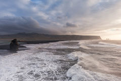 Black Sand Beach Reynisfjara in Iceland. Windy Morning. Cloudy Sky Stock Photo