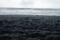 Black sand beach of Reynisfjara, Vik. The Black sand beach of Reynisfjara, Vik and the mount Reynisfjall from the Dyrholaey promontory and Volcanic rock in the royalty free stock photo
