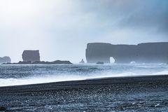 Black sand beach of Reynisfjara, Vik. The Black sand beach of Reynisfjara, Vik and the mount Reynisfjall from the Dyrholaey promontory and Volcanic rock in the royalty free stock images