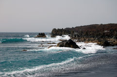 Black sand beach with rocks and waves Royalty Free Stock Images