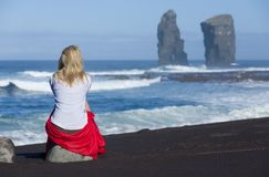 Beautiful blonde woman sits on beach stone, near to the iconic wild rock formations next to Mosteiros, in Sao Miguel island, Azore royalty free stock image