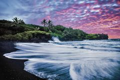 Black Sand Beach with Sunrise, Purple Sky, Waves, Green Vegetation and Lava Rocks in Maui, Hawaii stock images