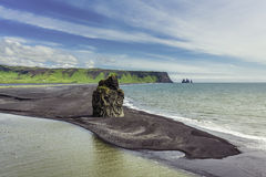 The black sand beach with typical Icelandic mountain Stock Image