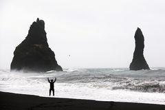 Black sand beach in Vik. Man get wet on a black sand beach in Vik, Iceland Stock Images