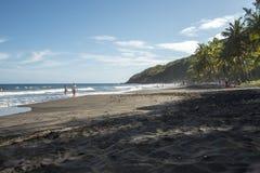 Black sand beach. Volcanic sand beach at Caribbean island Royalty Free Stock Photography