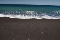 Black sand beach of Santorini island. Black sand beach and waves at Santorini island in Greece on a sunny day Stock Photo