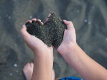 Black sand in children`s hands in the form of a heart royalty free stock images