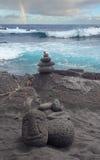 Black Sand Hawaiian Beach with Carved Tiki Head Rainbow in the S Royalty Free Stock Photo