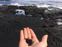 Black sand held in hand royalty free stock photos