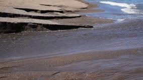Black sand volcanic beach with creek stock video