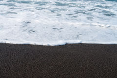 Black sand volcanic beach and sea wave Royalty Free Stock Images