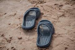 Black sandals on the beach sand. In Gandia, Spain stock image