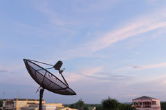 Black satellite dish. In community on blue sky background Stock Image