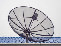 Black satellite dish on the blue roof. Royalty Free Stock Image