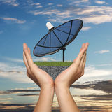 Black Satellite dish in hand of businessman on sunset background Royalty Free Stock Photos