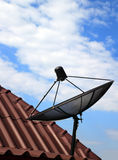 Black satellite dish on  house roof. And blue sky Royalty Free Stock Photo
