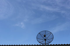 Black Satellite dish on roof in blue sky background. Royalty Free Stock Photos