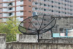 Black satellite dish and tv antenna at old village , parabolic digital receiver for communication data on roof stock photo