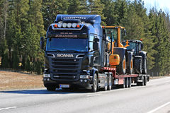 Black Scania R520 Hauls Machinery along Road. JOKIOINEN, FINLAND - MAY 1, 2017: Black Scania R520 semi trailer of J. Johansson transports machinery on lowboy Royalty Free Stock Images