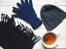 black scarf, a gray hat, blue gloves and a cup of tea on a white table Stock Image