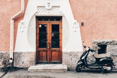 Helsinki, Finland – January 21, 2017: Scooter parked next to art decco house. Black scooter parked in front of the doors of a Jugendstil house royalty free stock image
