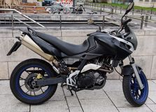 Black motorcycle standing on the sidewalk of a city street royalty free stock photo