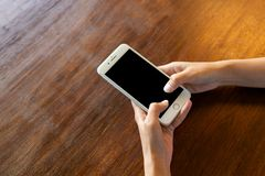 Black screen phone on wooden desk stock image