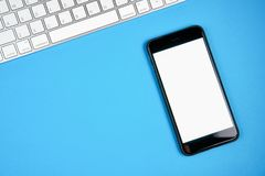 Black screen smartphone blank and keyboard with note pad placed on blue background. Royalty Free Stock Image