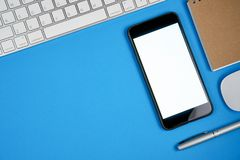 Black screen smartphone blank and keyboard with note pad placed on blue background. Stock Images